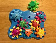 Jeu d'assemblage en plastique avec des engrenages de couleur que l'on peut actionner et des animaux à fixer dessus