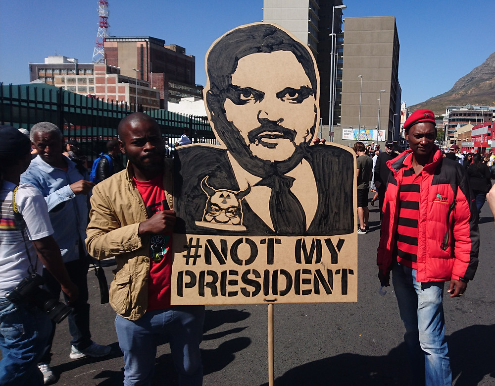 Protesters wearing the red of the EFF at an anti-Zuma rally carry a banner depicting Atul Gupta