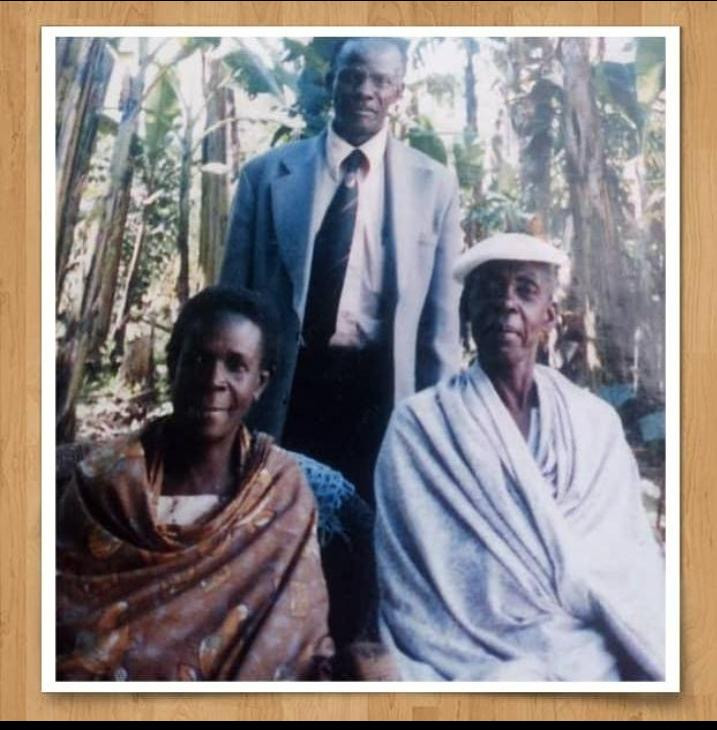 In this photo, the author's father Eliya Ngyendwa is pictured standing, with his wife (Siyadora Ngyendwa) seated on left and on his sister-in-law on the right (Edinans Kabagyenyi).