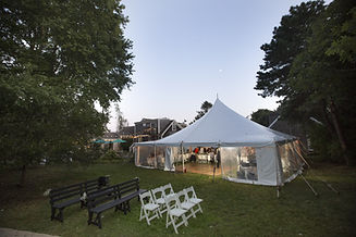 Party tent, benches and chairs in the backyard of the Rugosa on Cape Cod during sunset.