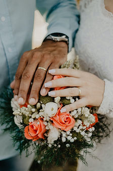 Hands of a bride and groom on top of a floral wedding bouquet.