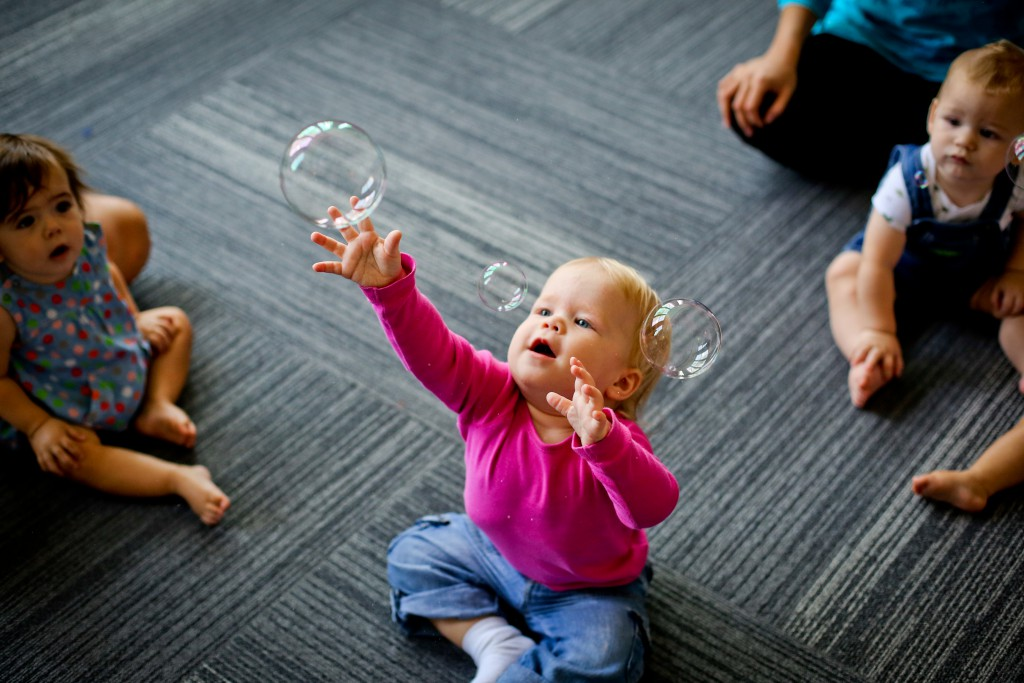 Kindermusik-2017_young_toddler_reaching_for_bubbles_close_up-1024x683