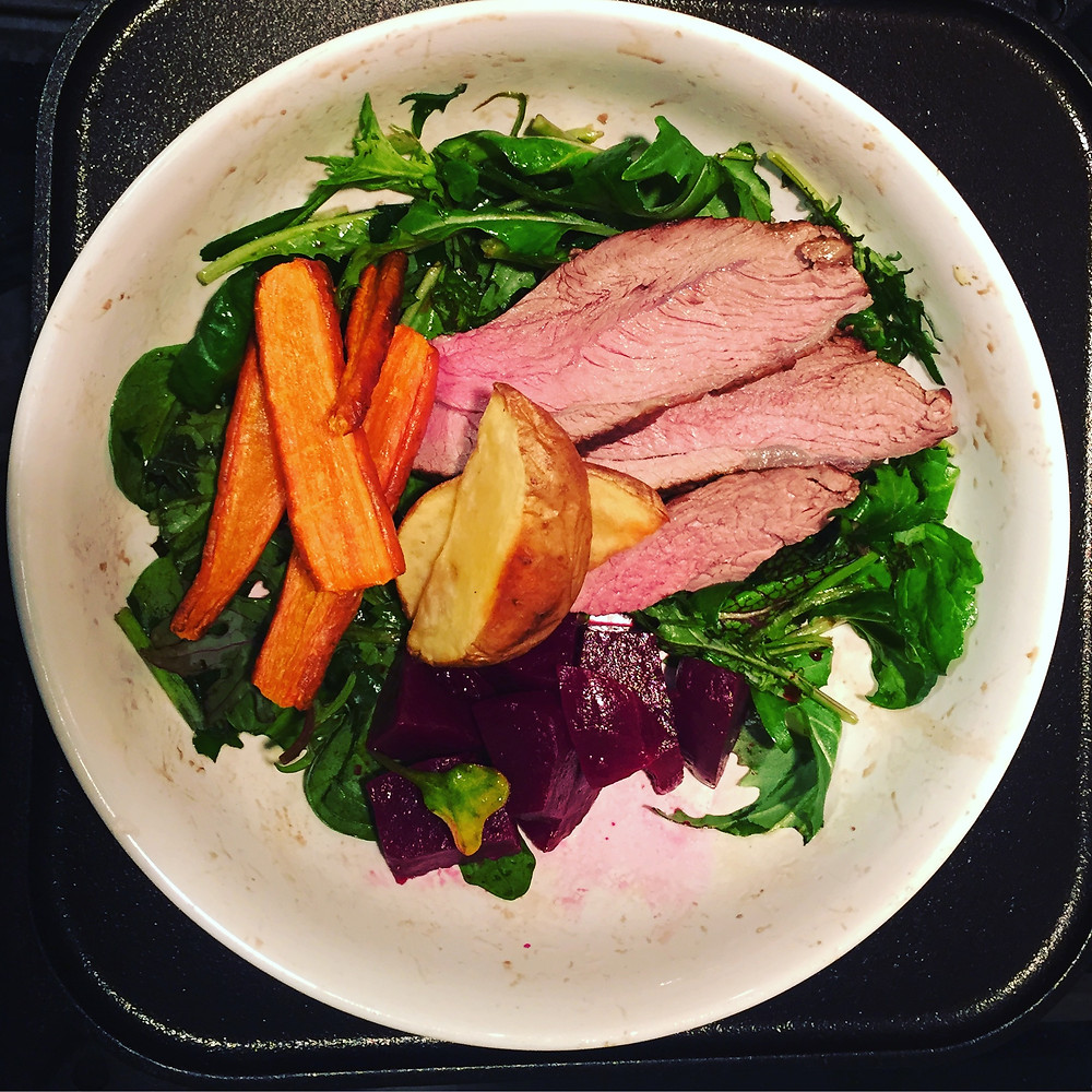 thin slices of lamb sirloin and veggies in a white bowl on a stove