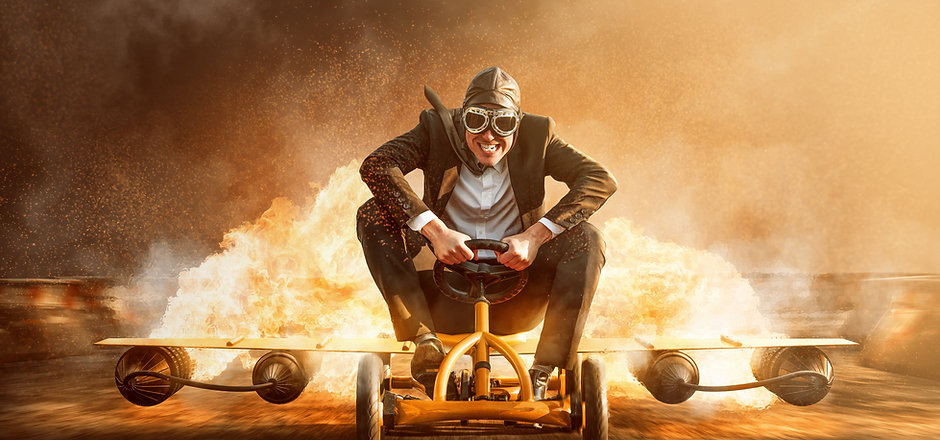 Businessman on a pedal car with a rocket