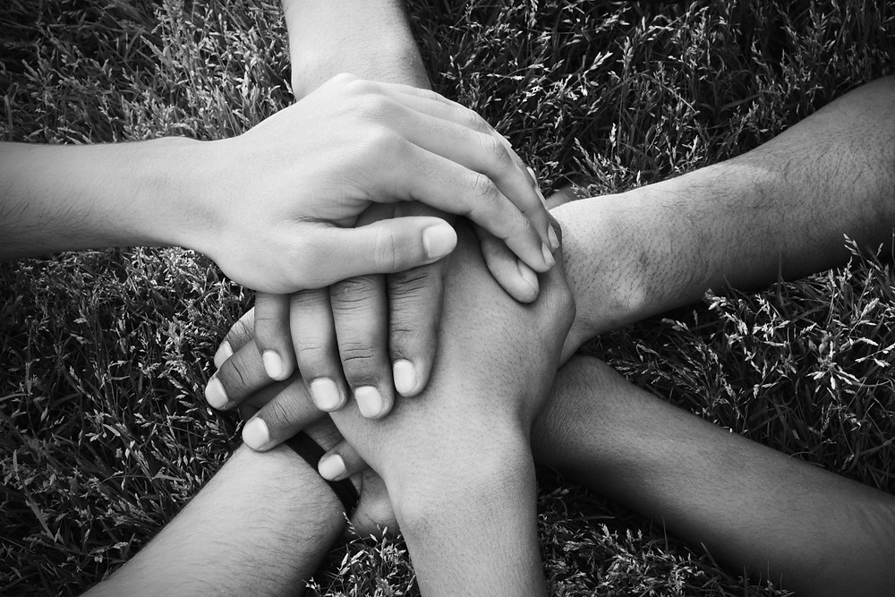 A group of people holding hands together.