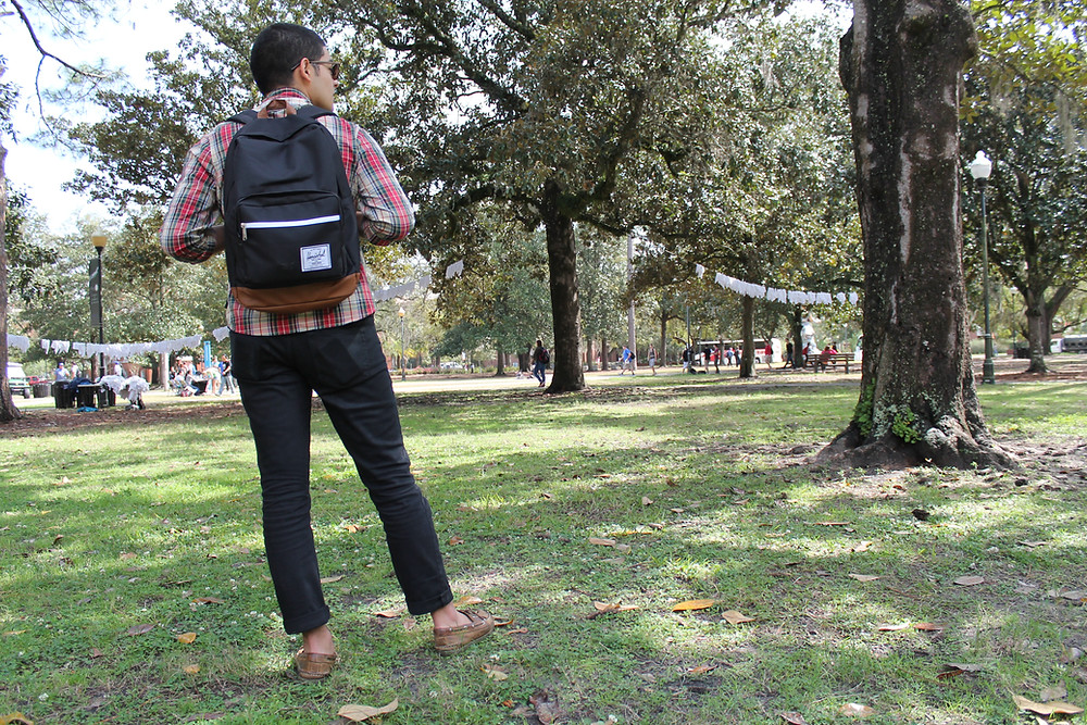 young person wearing backpack on campus