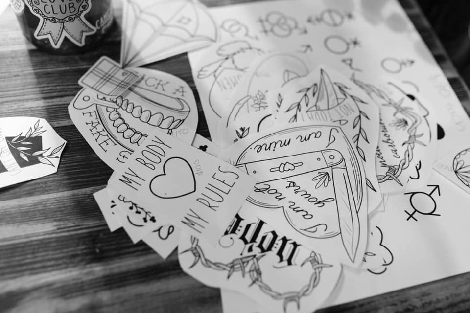 """Tattoo options on a table, including sayings like """"My body, my rules"""" and """"I am not yours. I am mine."""""""