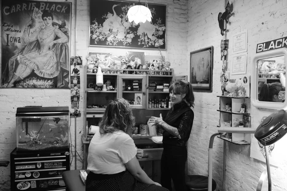 Tattoo artist discussing options with an enthusiast.