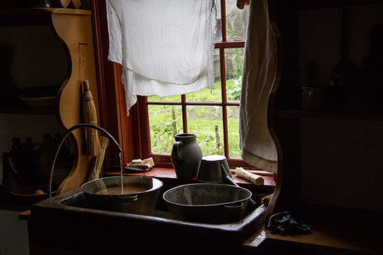 Farm Sink Window  #48  Deborah Putman  Farm Sink Window was captured at the Farmers Museum in Cooperstown, NY. Visitors are transported to another time in history. It's easy to imagine the woman of the house gazing out this window, taking a momentary break from her chores.  $90