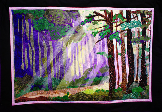 Whispers in the Forest  #25  Teri Pelton  Fabric  I was walking along a dirt road on a misty morning. Suddenly, a window in the sky opened up and the sun shone through. I took a photo and used it to inspire this quilted wall hanging. Just like the mist, this scene is best viewed from a distance.  NFS