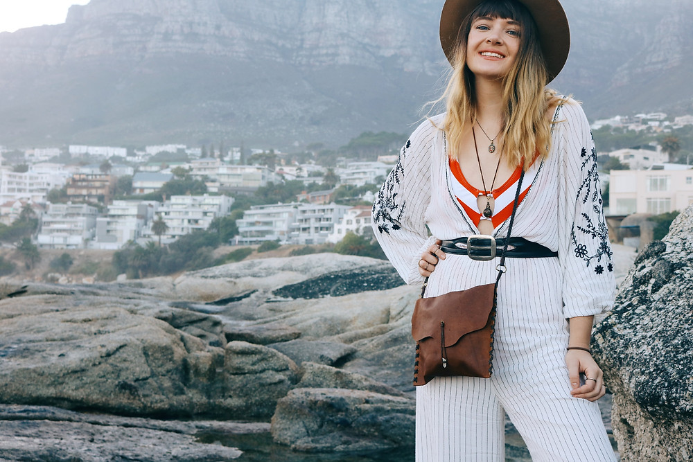 Model in jumpsuit smiling with mountain view in background