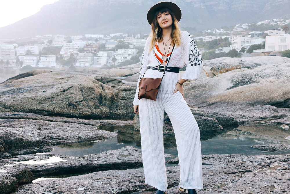 Model is wearing a jumpsuit and leather bag with ocean shore in background