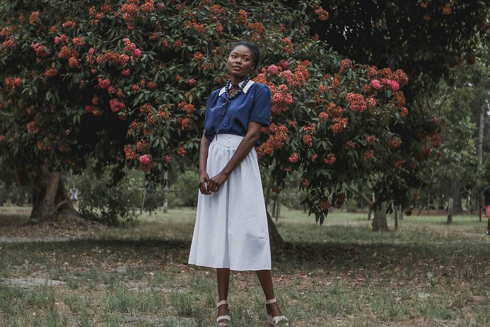 African model wearing white skirt standing in a park