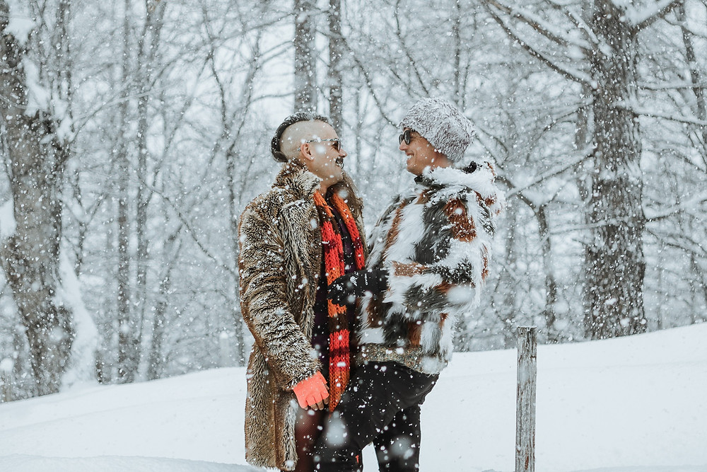 Gay male couple in the snow wearing furr coats