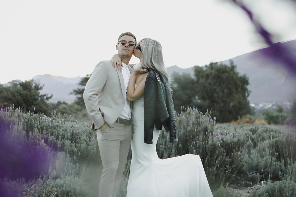 Bride and groom kissing each other in lavender flowers
