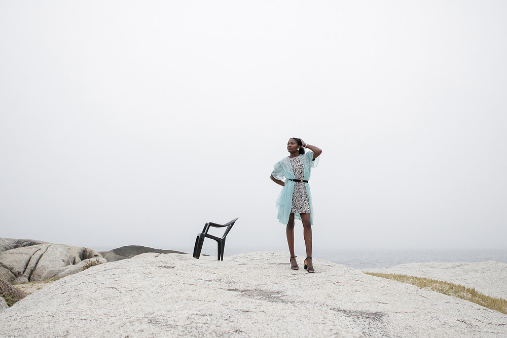 African model standing next to a plastic chair in a high fashion editorial look