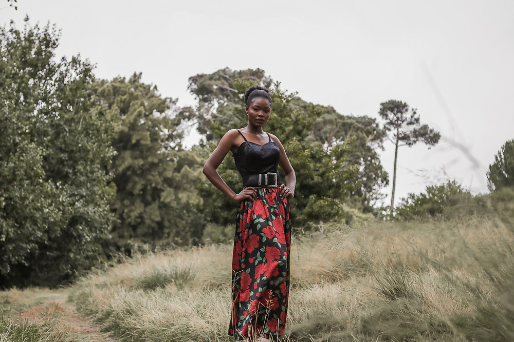 African model wearing rose dress and standing in park