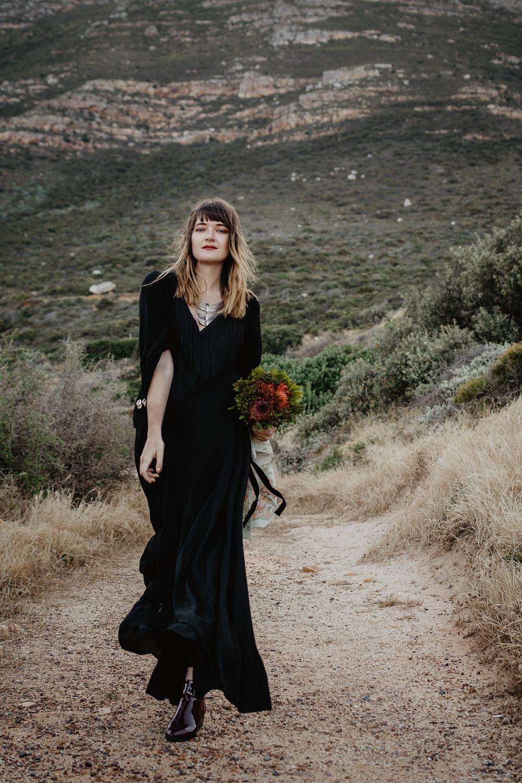 Model walking in black bohemian dress
