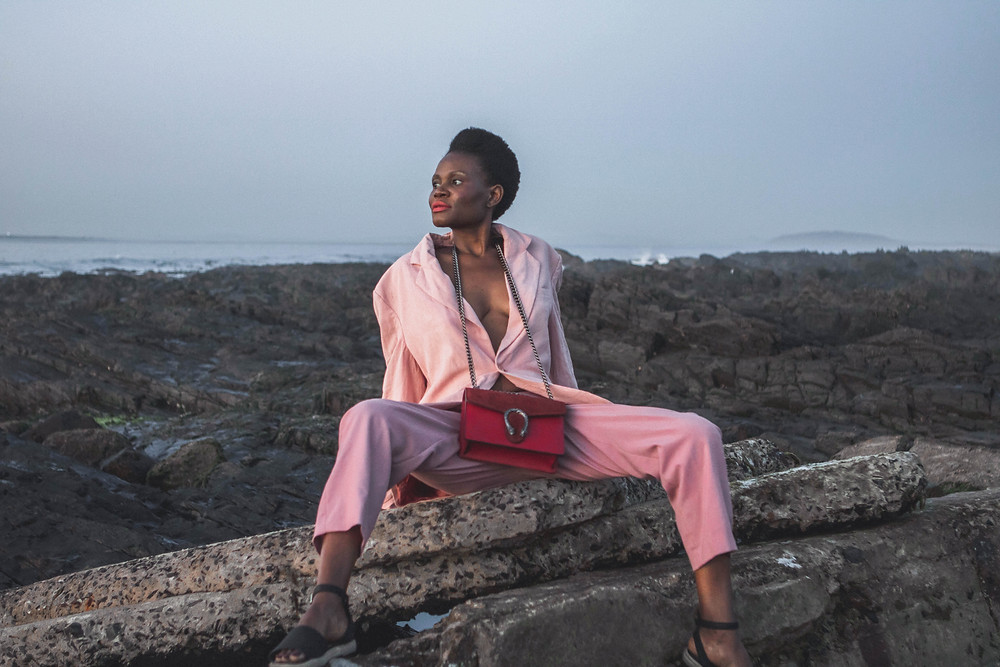 African model wearing pink blazer and pants with a Gucci purse