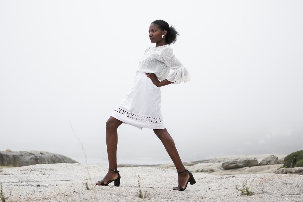 African model wearing white lace blouse and skirt on the beach