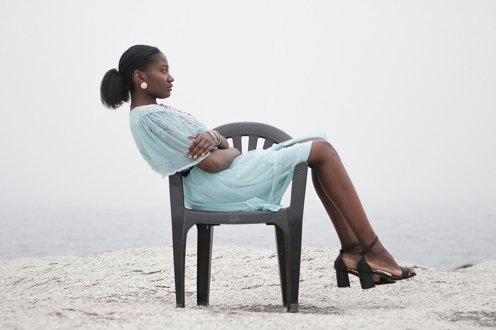 Model wearing blue dress sitting on plastic chair at the beach