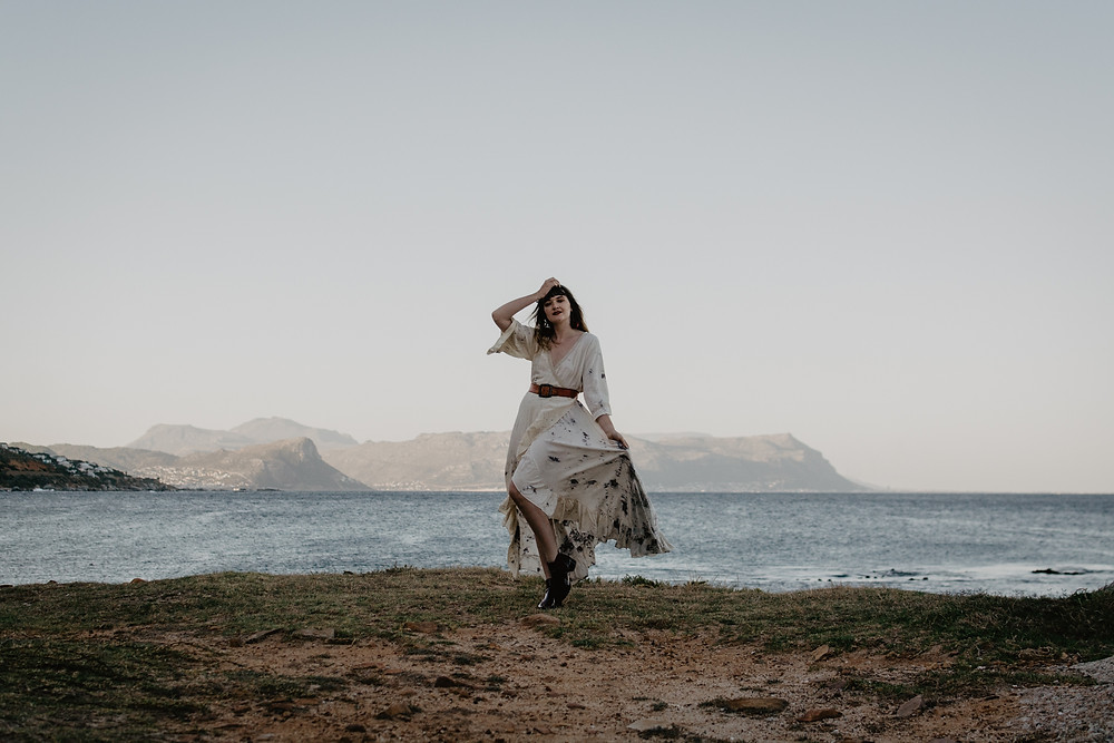 Model posing in bohemian dress with ocean view in the background