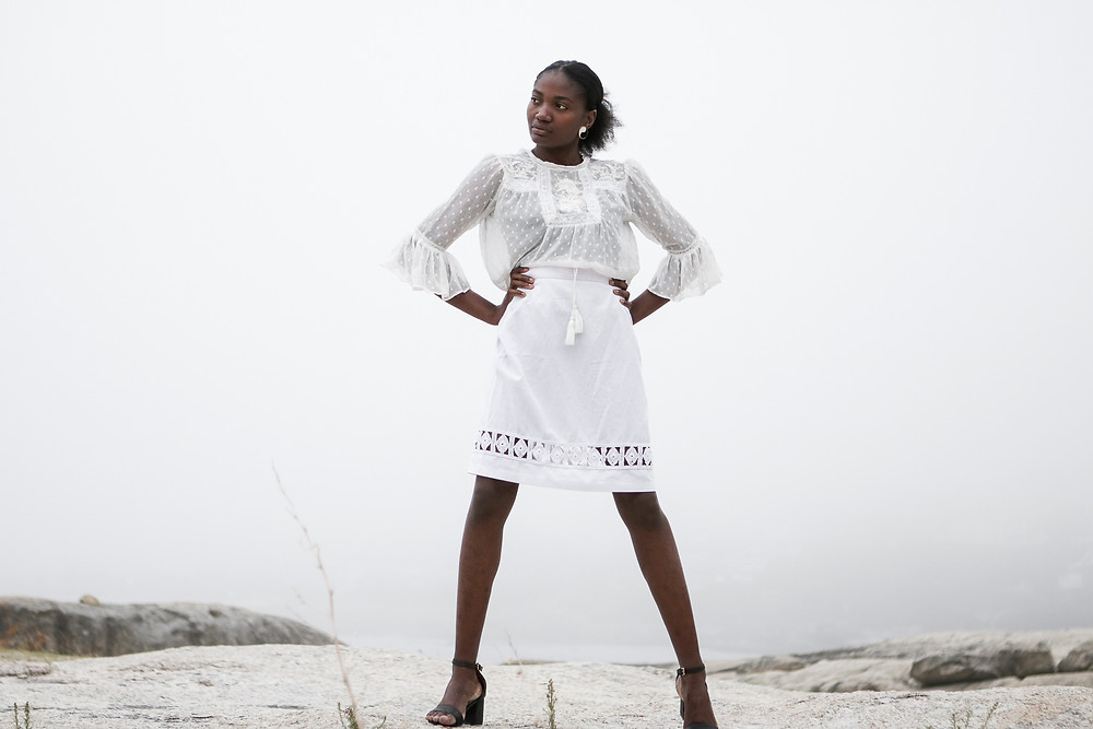 African female model wearing white lace blouse and white skirt