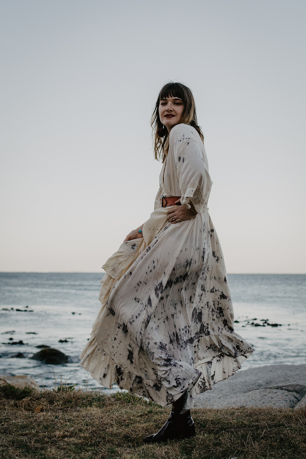 Model posing in bohemian dress with ocean view in background
