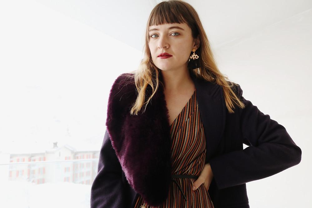 Model posing with fur purple coat and earrings