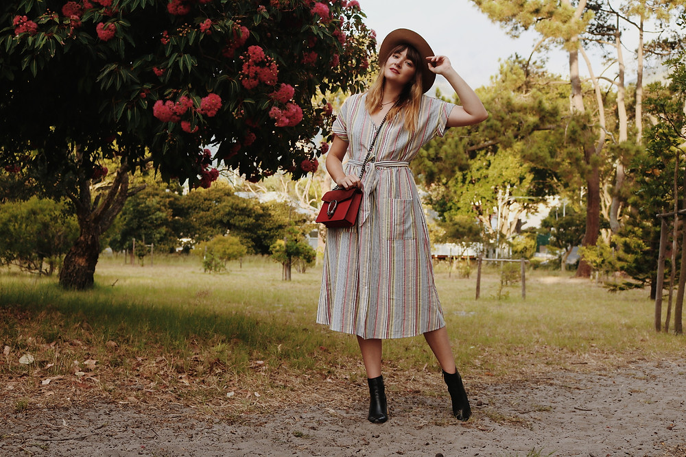 Model in striped dress holding a Gucci bag