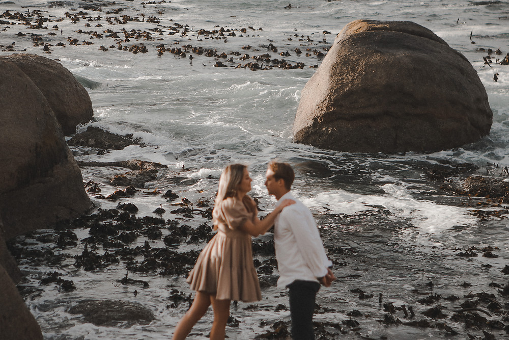 Engagement photoshoot of two couples kissing with the ocean in the background