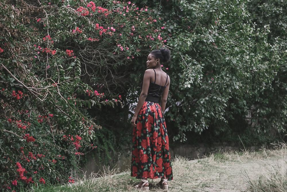 The model's back is turned wearing black velvet and silk rose patterened dress