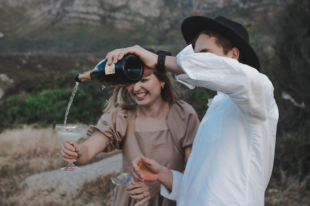 Engagement photoshoot of a couple drinking champagne