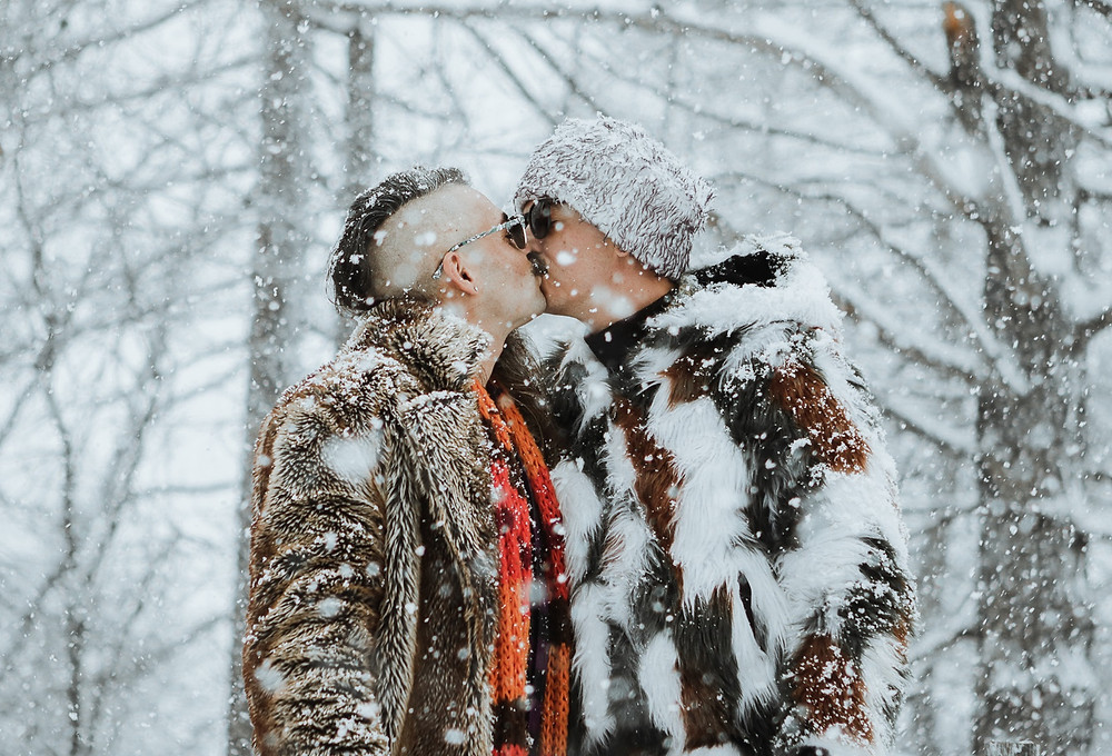 Gay male couple kissing in the snow
