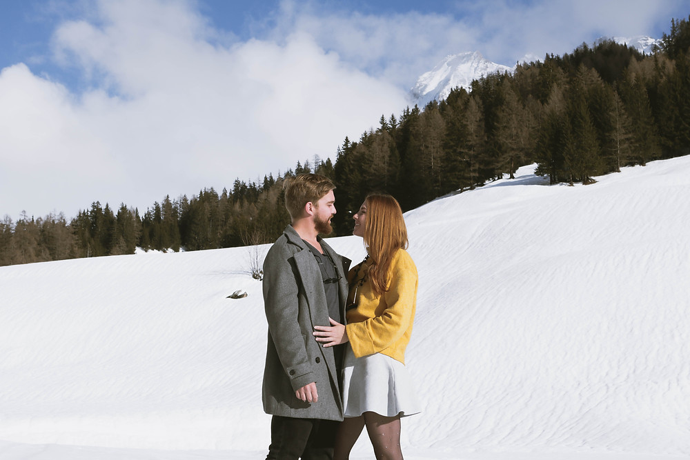 Couple staring lovingly at each other in the snow