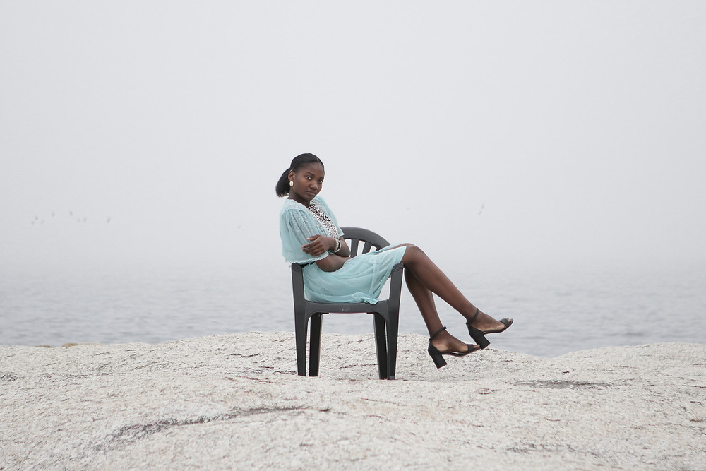 African model sitting on a plastic chair in a high fashion editorial look