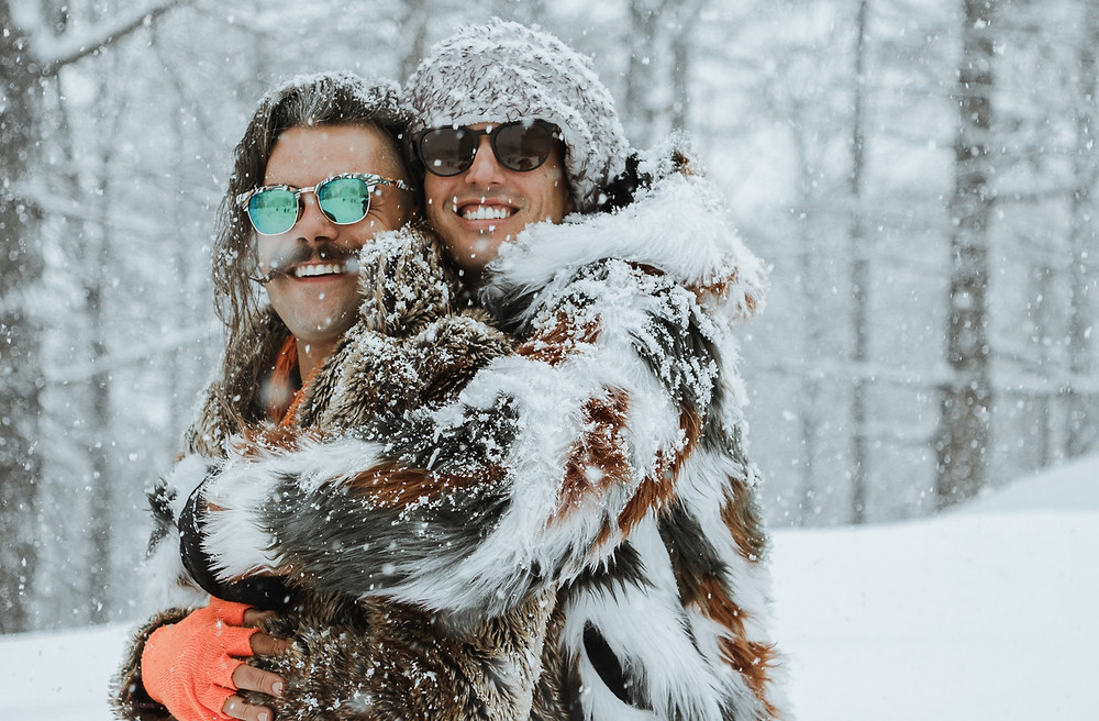 Gay male couple holding each other in the snow