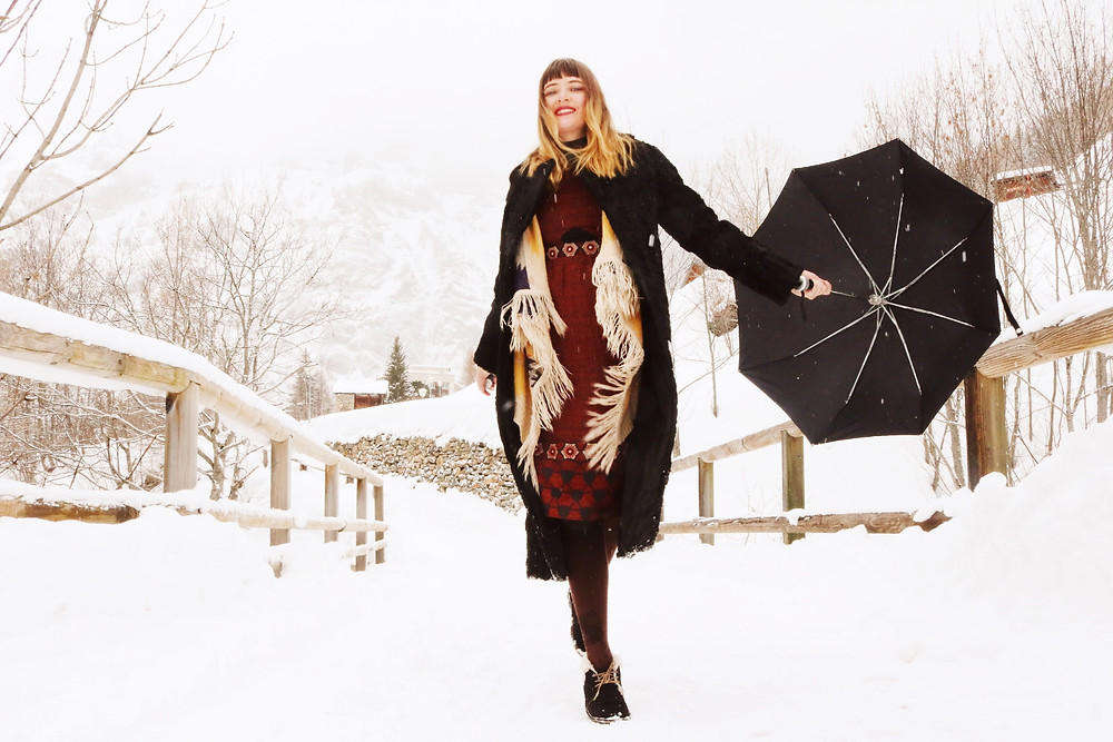 Model running in snow with umbrella