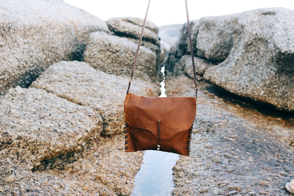 Leather bag with ocean shore in background
