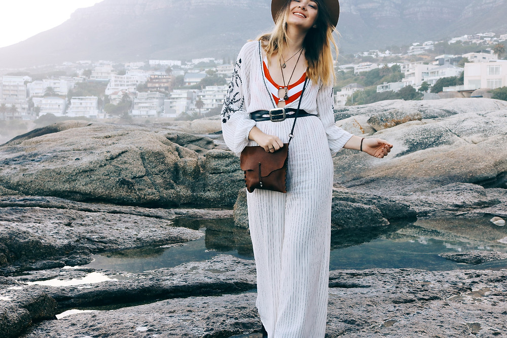 Model is wearing jumpsuit and leather bag with mountain view in background