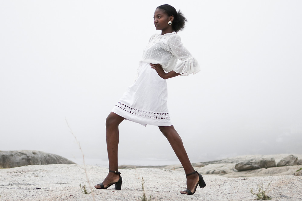 African model wearring a white embroidered sheer blouse.