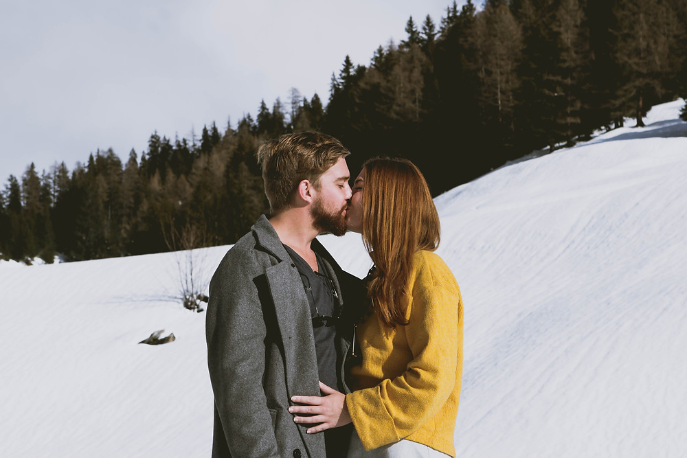 Couple kissing snow mountain views