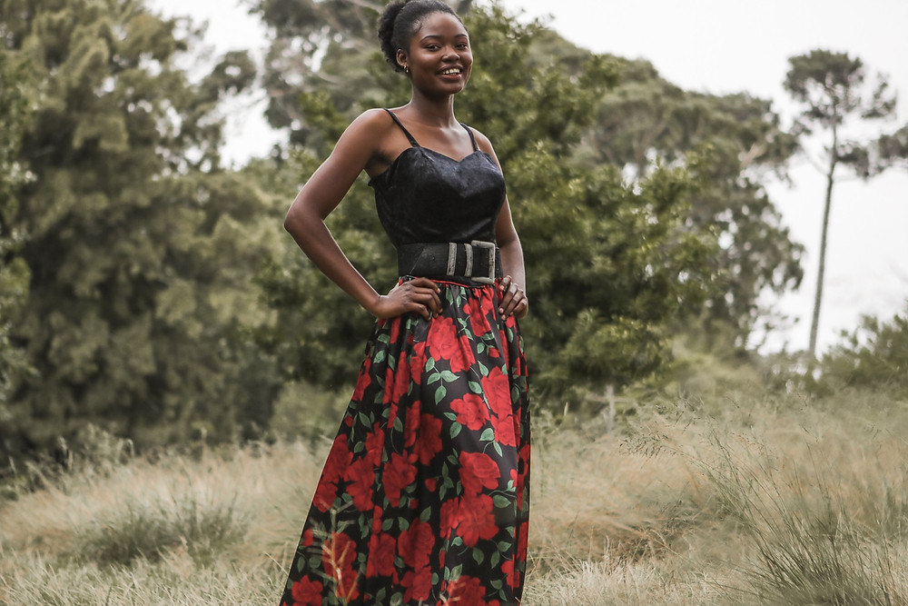 African model laughing while standing in a park and wearing a silk rose patterned dress