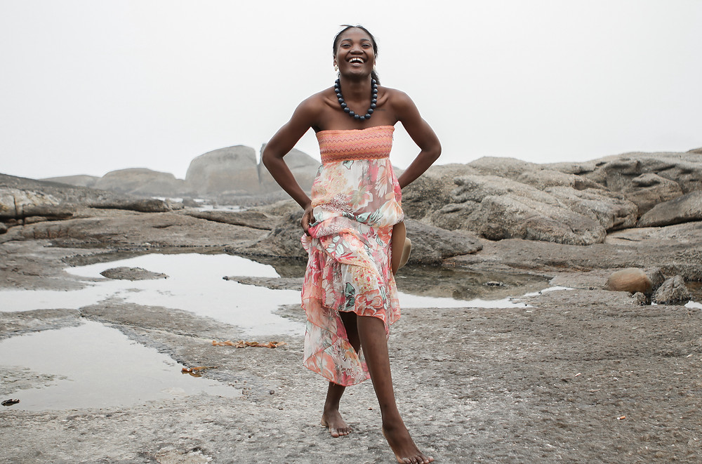 African female model wearing bohemian dress at the beach