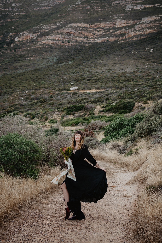 Model in black bohemian dress mountain view in background