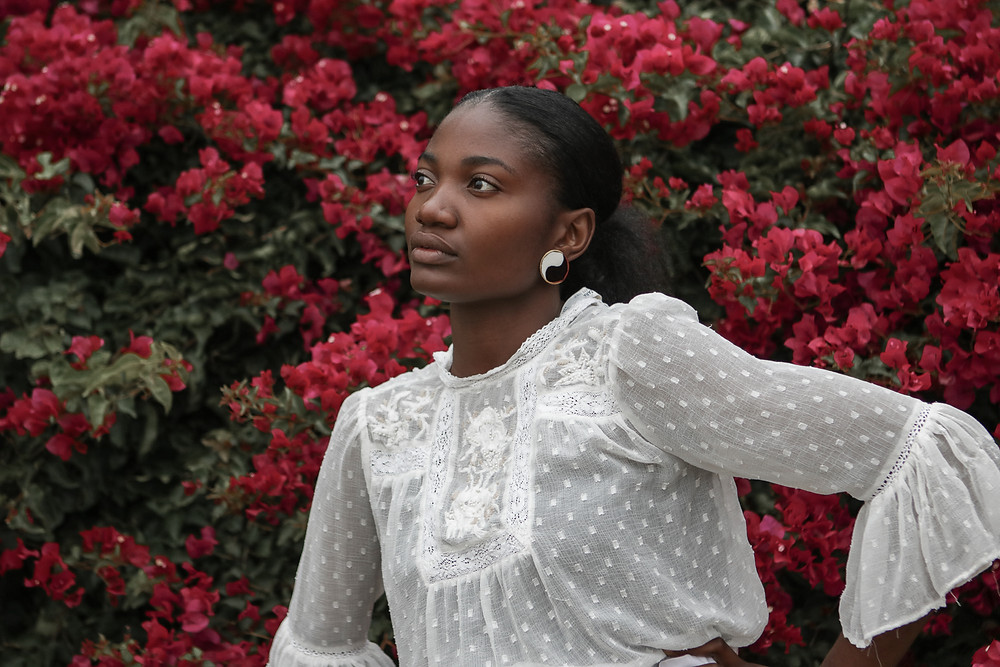 Portraiture of African female model wearing white lace blouse