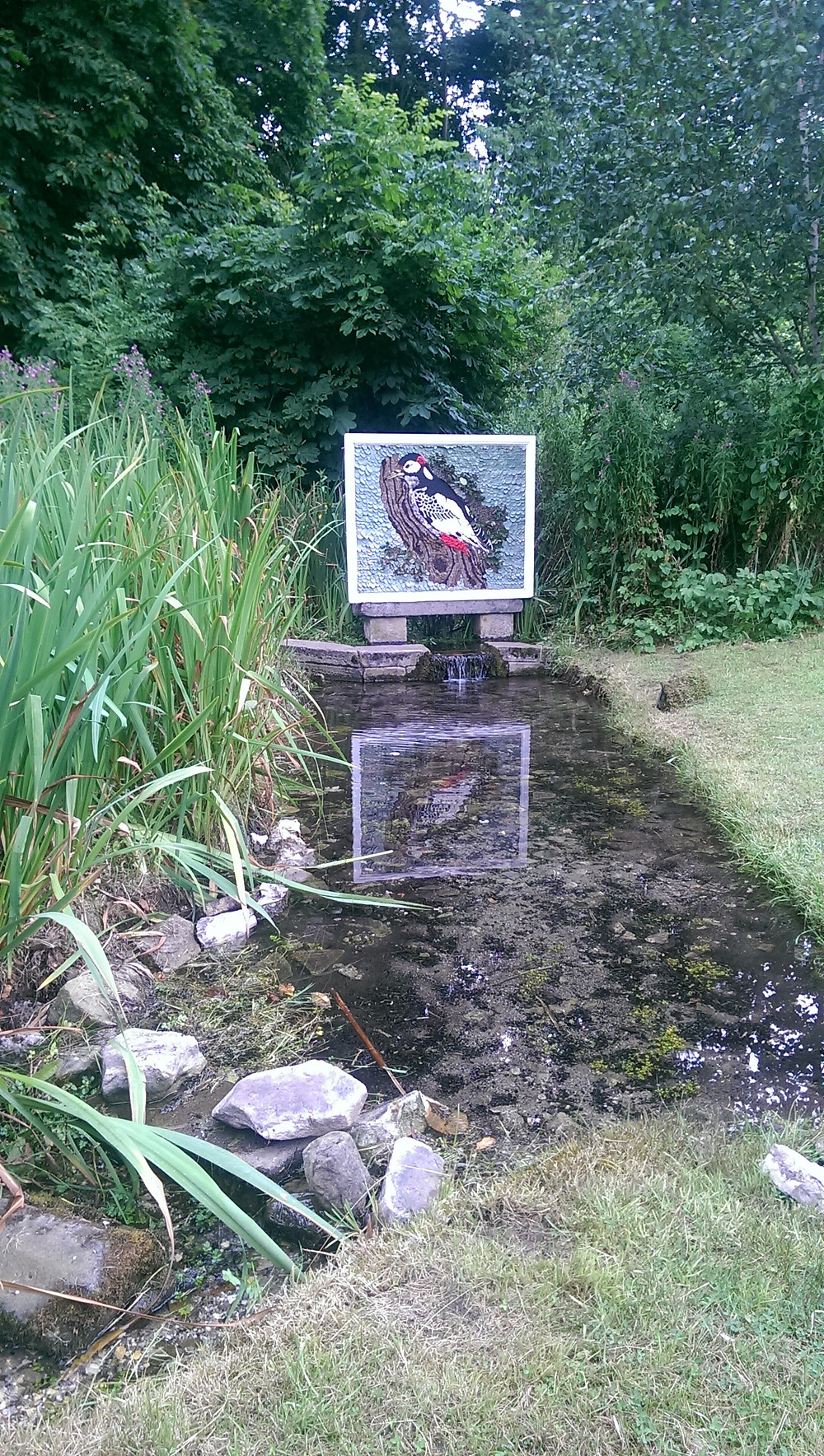 Woodpecker Well Dressing by The Old Roman Bathhouse in Stoney Middleton Peak District 2016