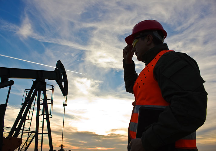 worker in the oil field industry at dusk