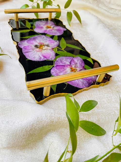 Purple phalaenopsis orchid in black acrylic tray
