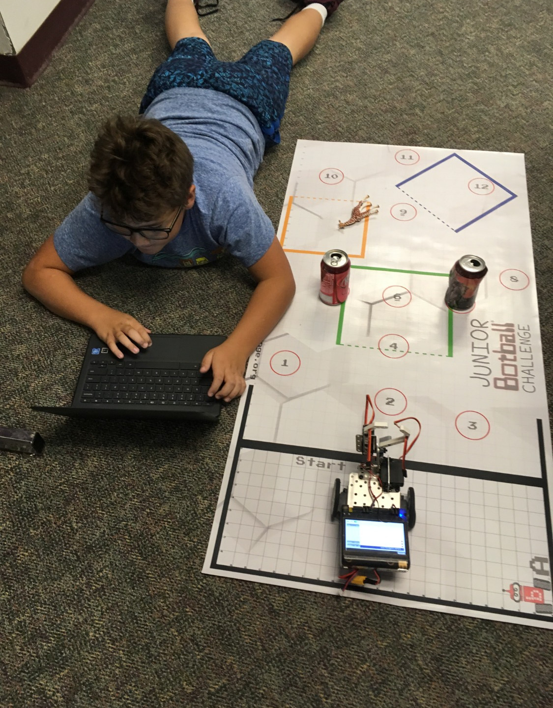 BMS Student challenged in class to get robot to hit a can or to manouver around them.